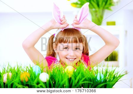 Easter holidays. Funny happy girl wearing bunny ears celebrating Easter at home.