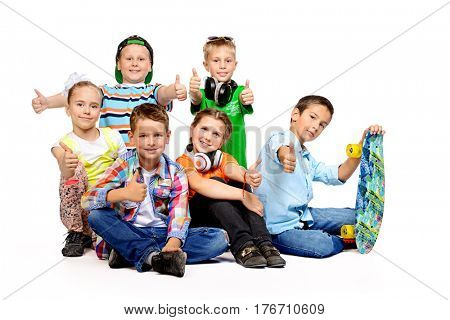 Group of happy children posing together at studio. Kid's fashion. Education. Isolated over white.