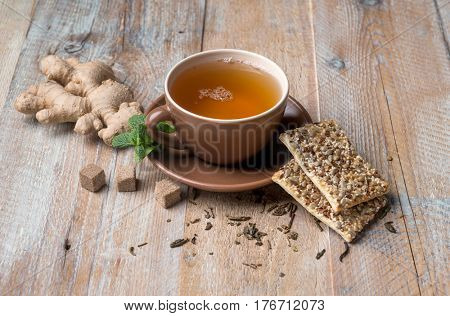 Aromatic cup of ginger tea, ginger on side, some cereal cookies with seeds, brown sugar