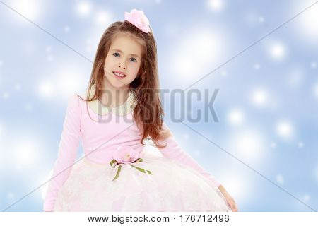 Dressy little girl long blonde hair, beautiful pink dress and a rose in her hair.She poses on the floor on his knees.Blue Christmas festive background with white snowflakes.