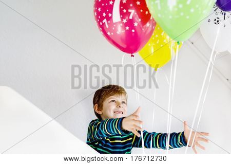 Portrait of happy kid boy with bunch on colorful air balloons on 7 birthday. Smiling school child having fun, celebrating seventh birth day. Family and best friend party.