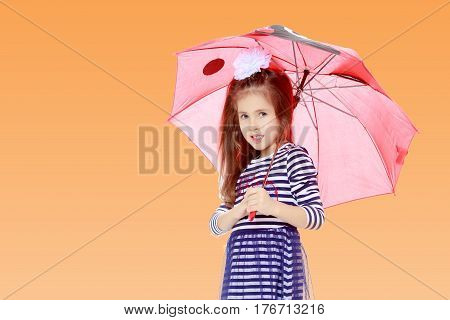Beautiful little girl long hair and white bow on her head , in a summer dress in stripes.She stands under the umbrella.