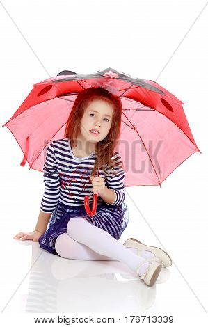 Beautiful little girl long hair and white bow on her head , in a summer dress in stripes.She's sitting on the floor hiding under the umbrella.Isolated on white background.