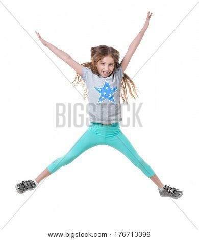 Active teen jumping high in the air, wearing green pants, isolated on white background