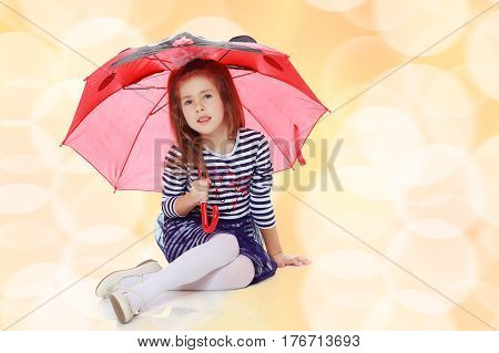 Beautiful little girl long hair and white bow on her head , in a summer dress in stripes.She's sitting on the floor hiding under the umbrella.Brown festive, Christmas background.