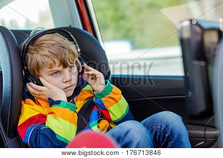 Little blond kid boy watching tv or dvd with headphones during long car driving on family vacations. Leisure for children for long drive. Preschool child sitting in safe car seat.