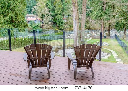 Two chairs on porch with a foret river view.