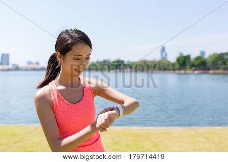 Woman using smart watch when running in park