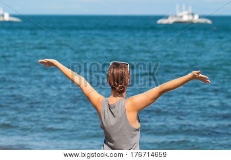 Woman with raised hands on the sea background. Happy girl in casual look on the seaside. Summer vacation freedom picture. Emotional gesture on the beach. Happy woman from the back in front of the sea