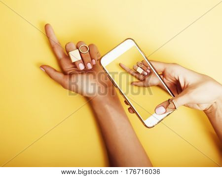 womans hand taking picture of her new manicure with fashion jewellery on her phone, girls stuff concept close up