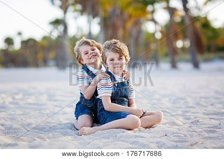 Two little kids boys having fun on tropical beach, happy best friends playing, friendship concept. Siblings brothers, twins in family look with palms on background. Family vacations on Jamaica