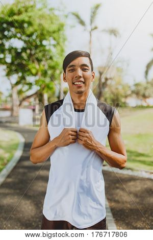 Portrait a man with white towel resting after workout sport exercises outdoors at public park Healthy lifestyle.