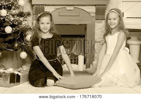 Cute little twin girls, sitting on the floor near the Christmas tree and electric fireplace on which candles are burning.Black-and-white photo. Retro style.