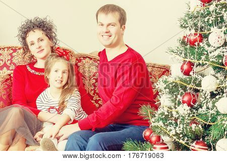 Happy parents with little daughter in a relaxed family atmosphere in the New year.Around the Christmas tree.Creative toning of a photograph.