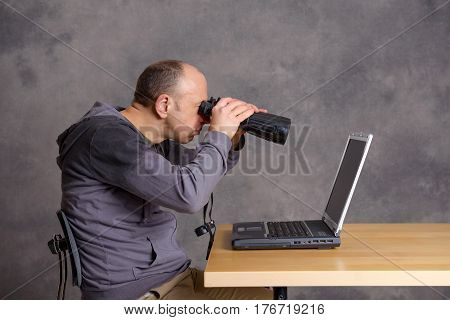 Young  Man Looking With Binoculars At The Screen