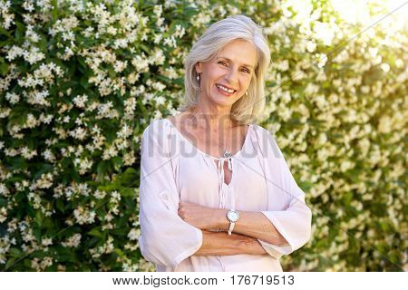 Older Woman Smiling And Standing Outside In Spring