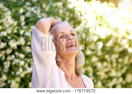 Carefree Older Woman Outside With Hand In Hair
