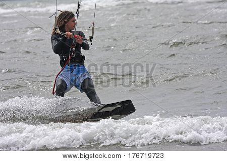 kitesurfer riding his board in the sea