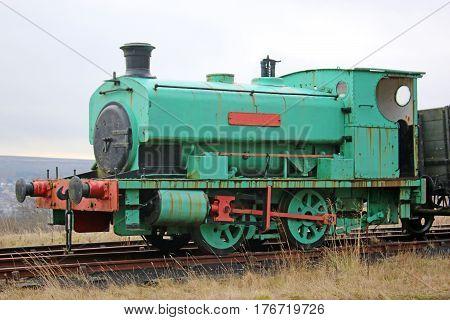 Vintage mining steam engine on rail tracks