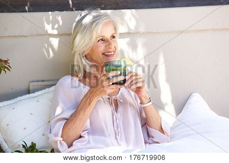Relaxed Older Woman Outside Drinking Tea With Lemon