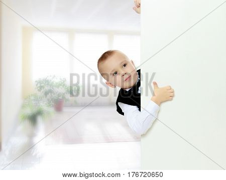 Cute little blonde boy in a black waistcoat and a white shirt and a bow at the neck , peeping over white banner.He holds up a thumb.In the Montessori room the children's garden where there are shelves with toys and material.
