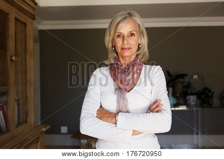 Serious Older Woman Standing In Study With Arms Crossed
