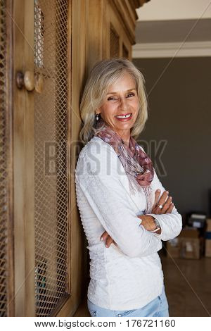 Beautiful Older Woman Smiling With Arms Crossed At Home