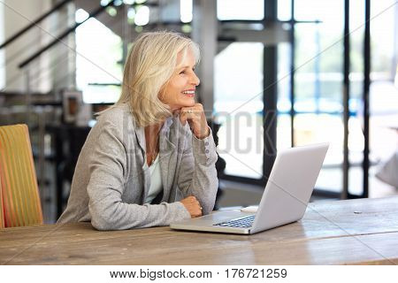 Smiling Older Woman Working Laptop Computer Indoors