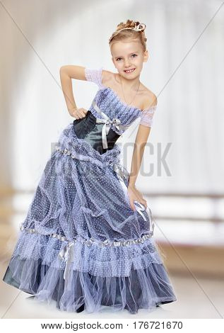 Slender little girl , with beautiful hair on his head, elegant long Princess dress.The girl twisted to the side and keeps his hand on his knee.In a room with a large semi-circular window.