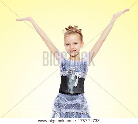 Slender little girl , with beautiful hair on his head, elegant long Princess dress.The girl raised her hands up and to the side.On a yellow gradient background.