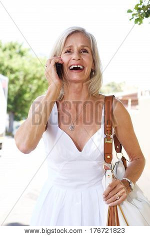Older Woman Outside Talking On Mobile Phone With Purse