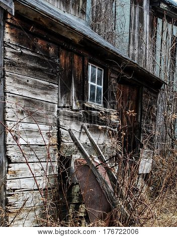 Old rusty Wheelbarrow leans against decrepit barn