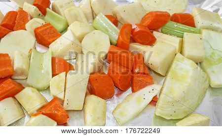 Potatoes, carrots, parsnips, cabbage and celery seasoned with pepper and drizzled with oil ready for roasting