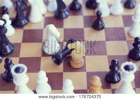 Two chess horses stand over the defeated figure of the rook / joint efforts bring victory closer