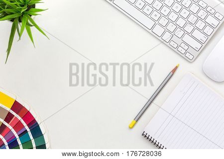 Workplace of professional Designer on white Office Table with colour palette multi coloured gamma Notepad Pen Computer and green Plant
