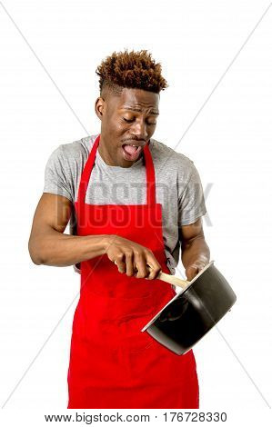 young desperate and confused black afro american man in chef apron holding cooking pot and spoon in his hands looking lost and overworked in male home cook concept isolated on white background