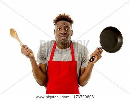 young desperate and confused black afro american man in chef apron holding cooking pan and spoon in his hands looking lost and overworked in male home cook concept isolated on white background