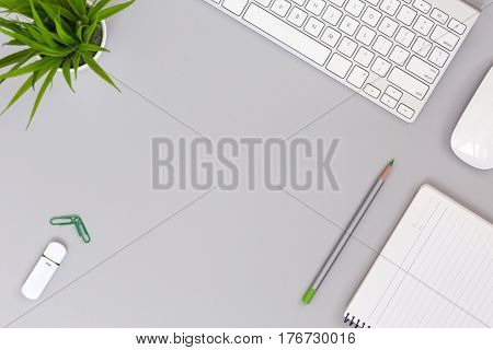 Neat and well ordered Working Place on grey Table with Business and Lifestyle Items Computer Cactus Paper Clips Pencil compact Flash Drive Notepad with blank Pages for copy Space flat top View.