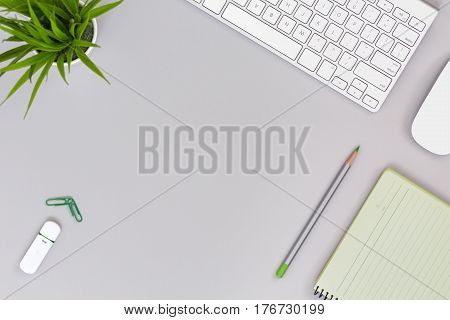 Neat and well ordered Working Place on grey Table with Business and Lifestyle Items Computer Cactus Paper Clips Pencil compact Flash Drive Notepad with green Pages for copy text flat top View.