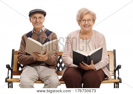 Elderly man and woman with books sitting on a bench and looking at the camera isolated on white background