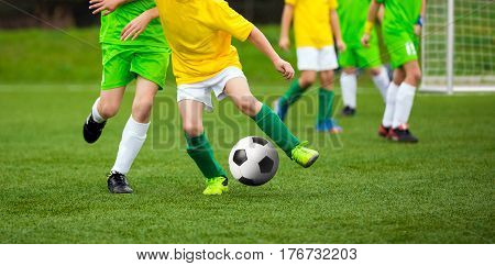 Football Player Running with the Ball on the Pitch. Footballers Kicking Football Match on the Pitch. Young Teen Soccer Game. Youth Sport Background