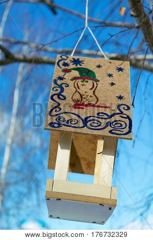A bird feeder with a roof. On the roof of a drawn figure. The animal depicted in the cap with a curved stick around patterns and snowflakes. Feeder hanging on a tree on a rope. It is made of wood.