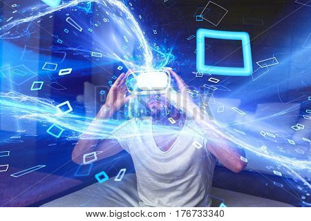 Young man with headset playing virtual reality with blue glowing media stream and particles