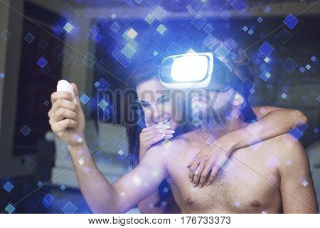 Young couple playing with virtual reality headset and blue glowing tiles