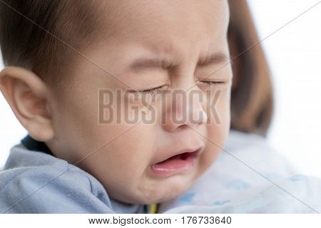 Portrait of 5 months Asian baby boy crying in mother arm.