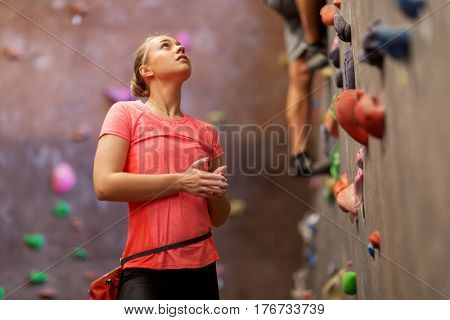 fitness, extreme sport, bouldering, people and healthy lifestyle concept - young woman exercising at indoor climbing gym
