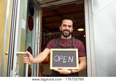 small business, people and service concept - happy man or waiter with open word on blackboard at bar or restaurant entrance door