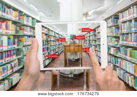 Augmented reality education concept. Hand holding digital tablet smart phone use AR application to check library category in bookshelf at university library.