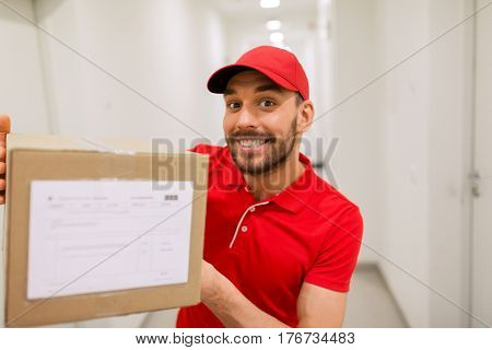 delivery, mail, people and shipment concept - happy man in red uniform with parcel box in corridor