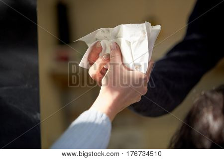 fast food, people and unhealthy eating concept - close up of woman hand buying hamburger on street